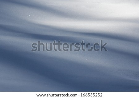 Silky soft velvet abstract shape blue long shadows on the white fresh snow in a superb winter decor detail - stock photo