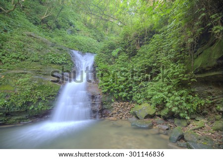 Silky waterfall in a secret ravine ~ Cool refreshing waterfall in a mysterious forest of lush greenery - stock photo