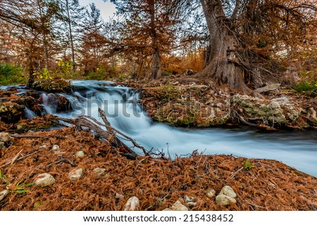 Silky Waterfall with Beautiful Fall Foliage Surrounding the Guadalupe River, Texas. - stock photo