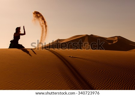 Sillhouette woman playing and throwing with sands in Desert Sahara, Morocco - stock photo