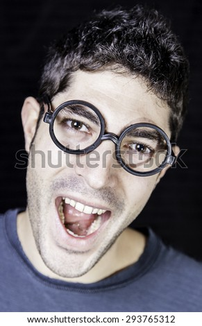 Silly boy with glasses, grimacing and expression - stock photo