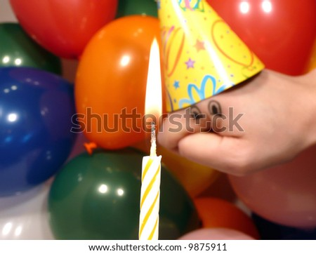 Silly hand puppet dressed up for a birthday party looking at a lit candle
