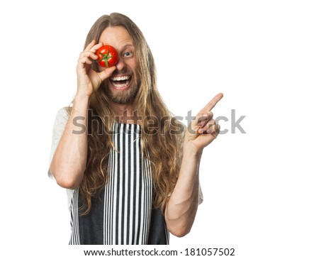 Silly hippie holding a tomoto over his eye and pointing at copy-space. Isolated on white. - stock photo