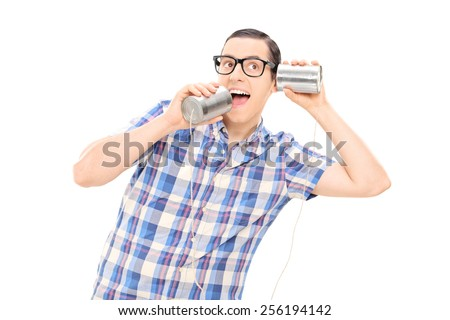 Silly man talking to himself through tin can phone isolated on white background - stock photo