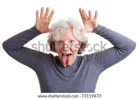 Silly old senior woman showing her tongue and making a face - stock photo