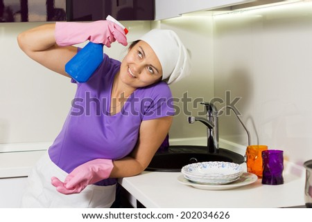 Silly woman holding spray cleaner to her head near the kitchen sink - stock photo