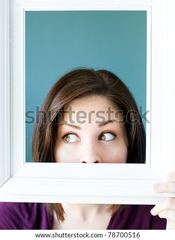 Silly woman peeking out from a white vintage picture frame. - stock photo