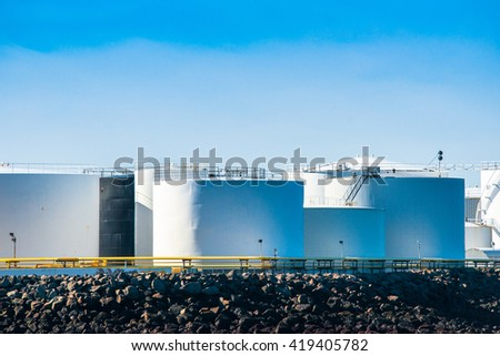 Silos in white by the sea in blue sky
