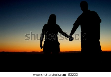 Silouette of a couple at sunset - stock photo