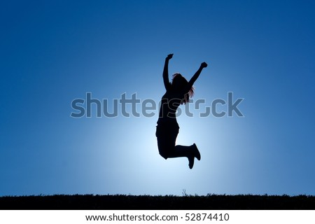 silouhette of a female in the sun jumping in victory - stock photo