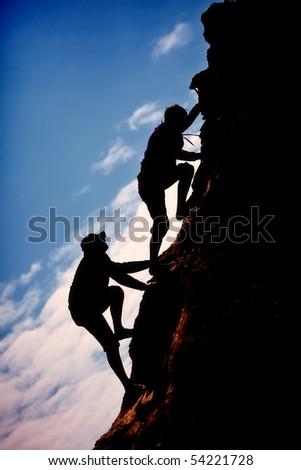 Siluet two men climb up the mountain - stock photo