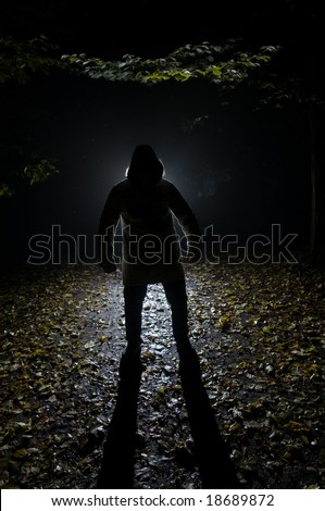 Siluette of man in the forest on the night - stock photo