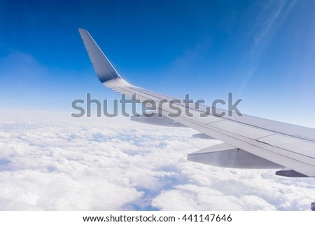 Silver Airplane Wing from Window Seat with Blue Sky and Clouds