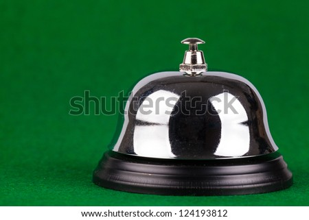Silver alarm service bell on green background - stock photo