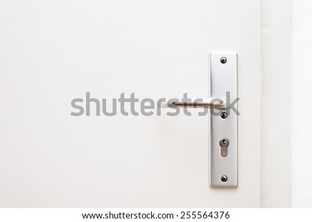 Silver aluminium modern metal door knob / door handle on a white wooden door, closed, horizontal