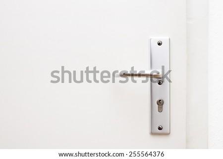Silver aluminium modern metal door knob / door handle on a white wooden door, closed, horizontal - stock photo