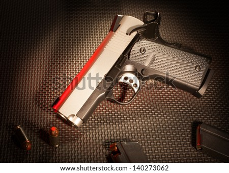 Silver and black semi automatic handgun, ammo and magazines - stock photo