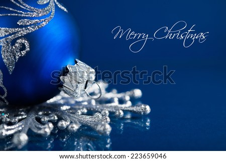 Silver and blue christmas ornaments on dark blue background with space for text.  - stock photo