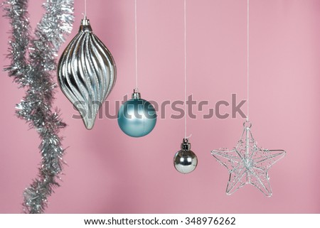 Silver and blue ornaments for Christmas and New Year hanging with pink background - stock photo