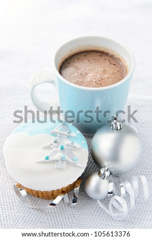 Silver and blue theme christmas; snowy frosty icy cupcake with xmas tree motif with baubles, ribbons and mug of hot chocolate - stock photo