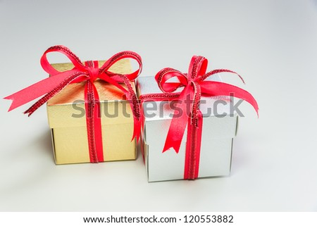 silver and gold small gift box with red ribbon in row on white background