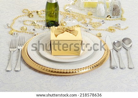 silver and gold table setting with present - stock photo