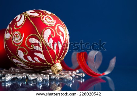 Silver and red christmas ornaments on dark blue background with space for text. Merry christmas card. Winter holidays. Xmas theme. - stock photo