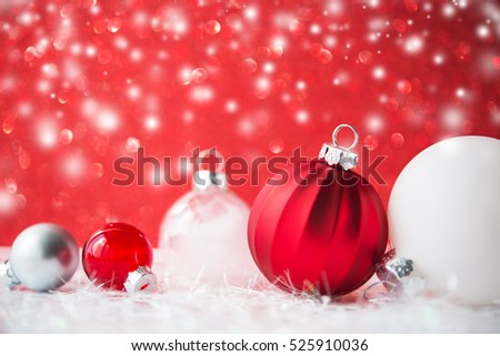 Silver and white christmas ornaments on red glitter bokeh background with blurred snow. Merry christmas card. Winter holiday xmas theme. Happy New Year. Space for text.