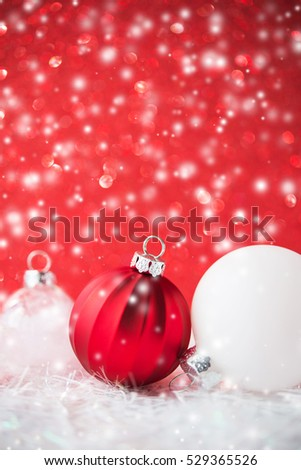 Silver and white christmas ornaments on red glitter bokeh background with blurred snow. Merry christmas card. Winter holiday xmas theme. Happy New Year. Space for text