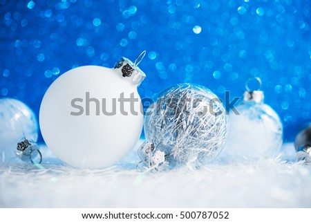 Silver and white xmas ornaments on blue glitter bokeh background. Merry christmas card. Winter holiday theme. Happy New Year.