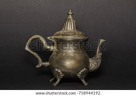 Silver antique teapot on a black background.