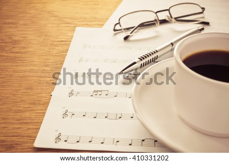 Silver ballpoint pen,eye glasses on music note paper .music note paper,cup of coffee on wood background.Write a song or music concept.Create music note paper this myself. - stock photo
