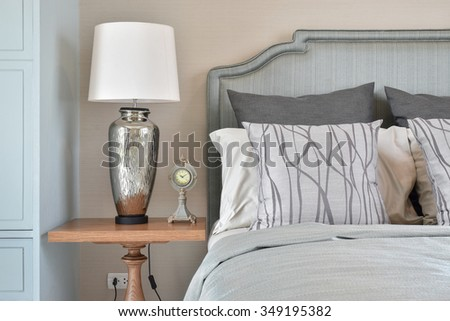 Silver base table lamp with clock and classic gorgeous bedding style - stock photo