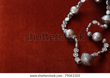 Silver bead necklace on an orange brown background