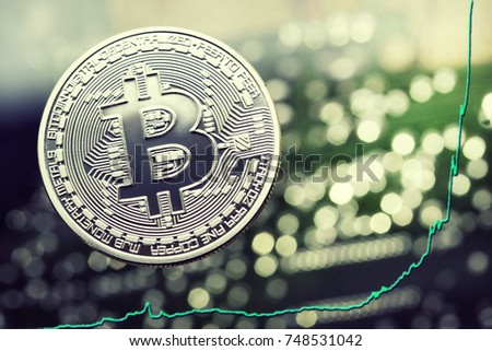 silver Bitcoin virtual currency coin on a circuit board background