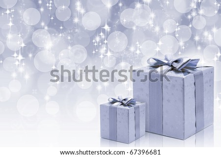 Silver boxes with bow against bokeh background - stock photo