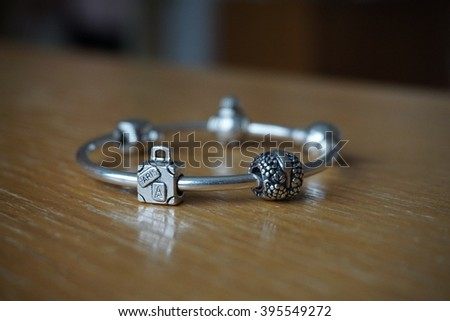 Silver bracelet with a collection of symbolic beads in various shapes, suit case as a traveling symbol