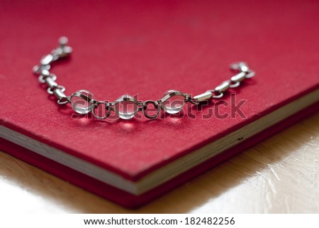 Silver bracelet with crystal balls laying on a red book - stock photo