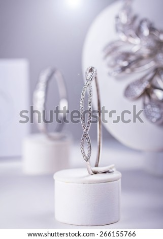 Silver bracelet with small diamonds. Isolated on grey. Lens flare. Small depth of field - stock photo