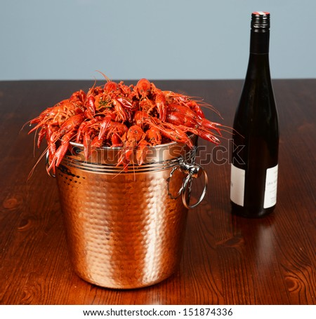silver bucket of boiled crawfish served with wine - stock photo