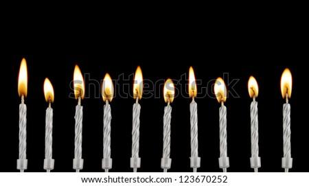 Silver burning candles on black background - stock photo