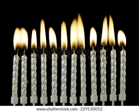 Silver burning candles on black background
