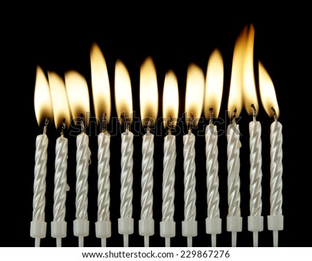 Silver burning candles on black background - stock photo