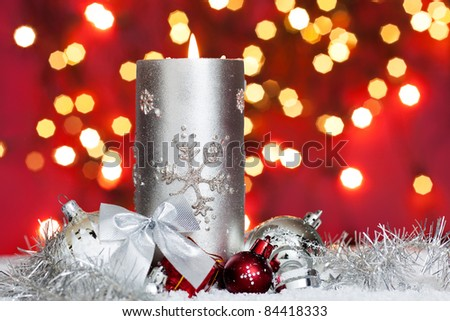 silver candle with christmas balls in snow with lights in background - stock photo