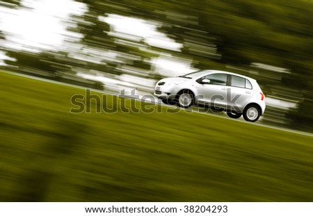 silver car on a countryside road - stock photo