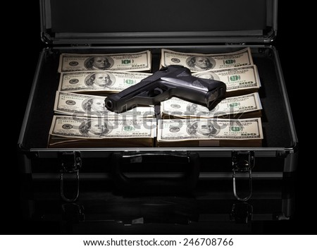 Silver case with money and gun on black background