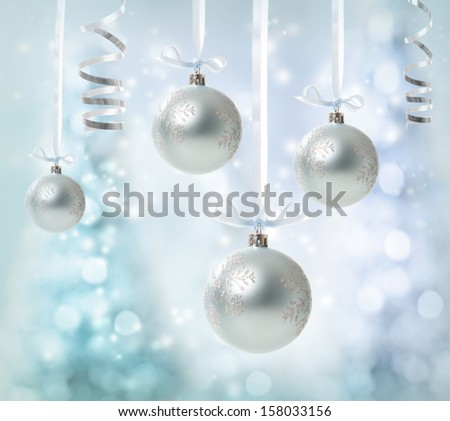 Silver Christmas Ornaments over glowing tree background - stock photo