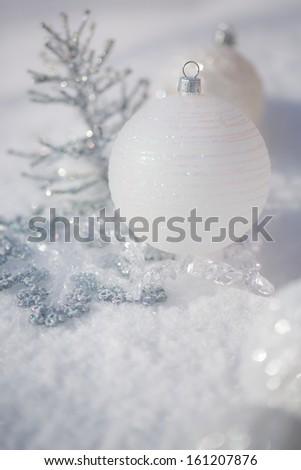 Silver Christmas tree decorations on real snow outdoors. Winter holidays concept. Shallow depth of fields