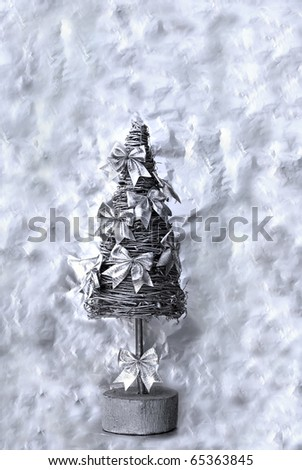 Silver christmas tree with decorative bows on the abstract background