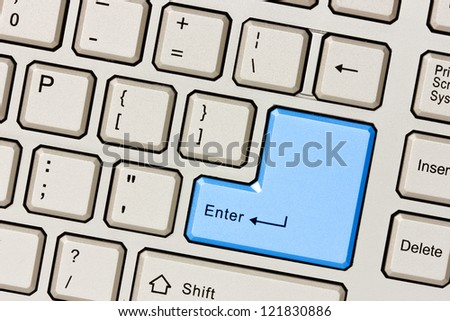 Silver computer keyboard with blue Enter key - stock photo